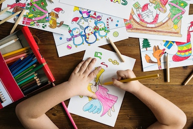 Child drawing and coloring images on paper