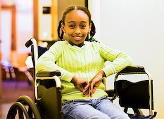 Female pediatric patient smiling while sitting in a wheelchair