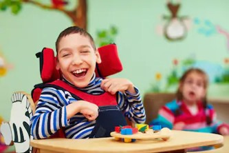Male pediatric patient smiling while sitting in a high chair